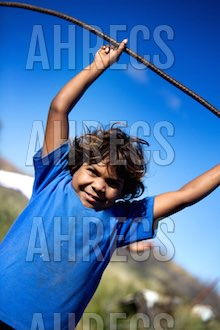 Smiling Indigenous boy holding a stick above his head