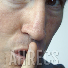 Covert: Close up of a man's face as he holds a finger to hyis lips shhhh