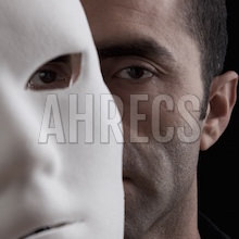 The face of a black man partially revealed behind a white mask.