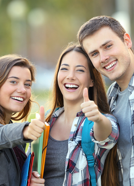 Three young students look toward us and give us a thumbs up
