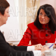 Two serious women in a meeting sitting at a table in the office together analysing paperwork