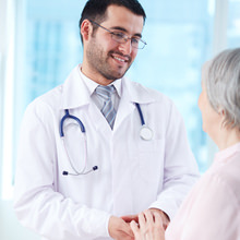Confident doctor looking at his senior patient while speaking to her