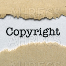 The copyright seen through a strip torn out of a brown sheet of paper