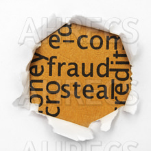 Word cloud around the concepts of fraud and steal viewed through a ripped hole in a piece of paper