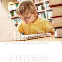 Schoolkid working with laptop in the library
