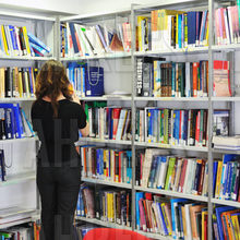 Woman browses shelves of books and magazines in modern library