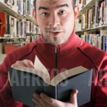 Young man in a library looks up from a book with a surprised