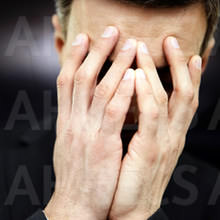 A man cradling his face in his hands