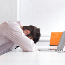 Frustrated young man as head pressed down on arms and desk in front of his open laptop