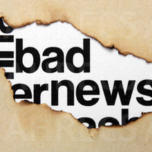The words 'Bad news' seen through torn paper