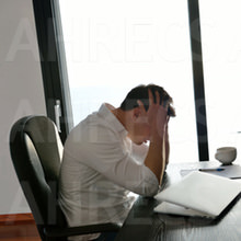 Distraught young man clutches his head in front of a partially closed laptop