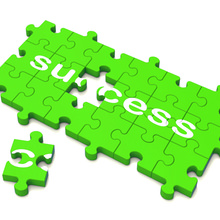 The word 'Success' on a green jigsaw puzzle with the final piece just about to be added.