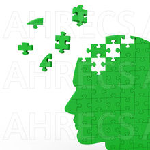 Green silhouette of a head comprised of jigsaw pieces with some flying loose.