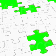 White jigsaw puzzle with some missing pieces on a lime green backing that shows through the gaps