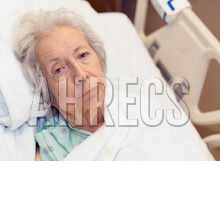 White-haired woman in hospital bed looks despondent