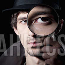 A detective peering through a magnifying glass