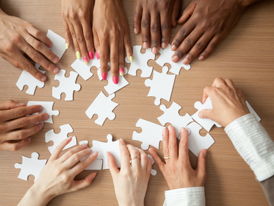 A circle of hand around a table solve a tricky jigsaw