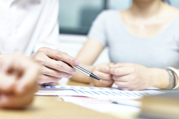 A woman holds pen, which is poised to make a note on a document