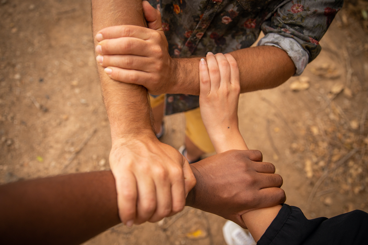 Three multi-racial arms griped together