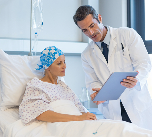 An oncologist showing a patient some written information