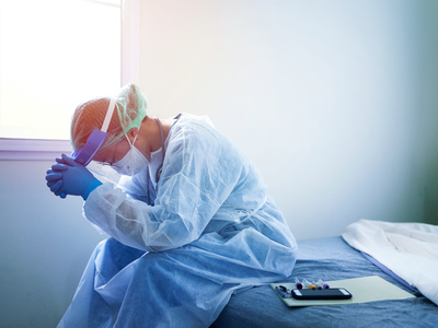 Clinician wearing sits bowed by anguish
