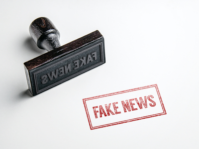 """An ink stamper and the stamped words """"FAKE NEWS"""""""