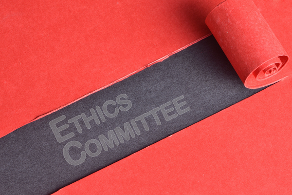 "The words ""ETHICS COMMITTEE"" seen through a curled rip of paper"