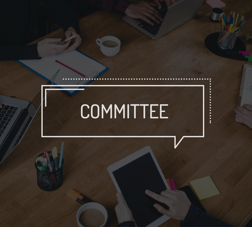 "Dark translucent meeting table wth the words ""COMMITTEE"" written across it"