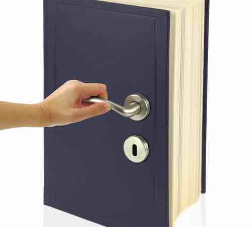 A hand opening a book with a keyhole on the front