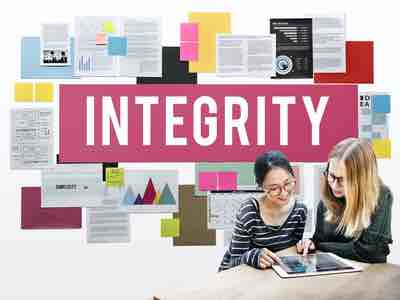 """Two young women reviewing a document about integrity in front of a wall of related items and a sign that reads """"Integrity"""""""