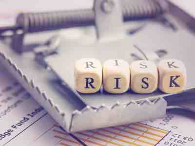 """A row of dice sitting on the trigger of a metal trap displaying the word """"RISK"""""""