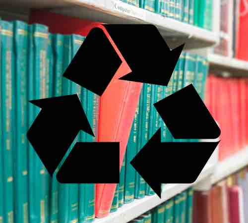 Recycling symbol overlaid a book in a bookshelf standing out at university library. Selective focus