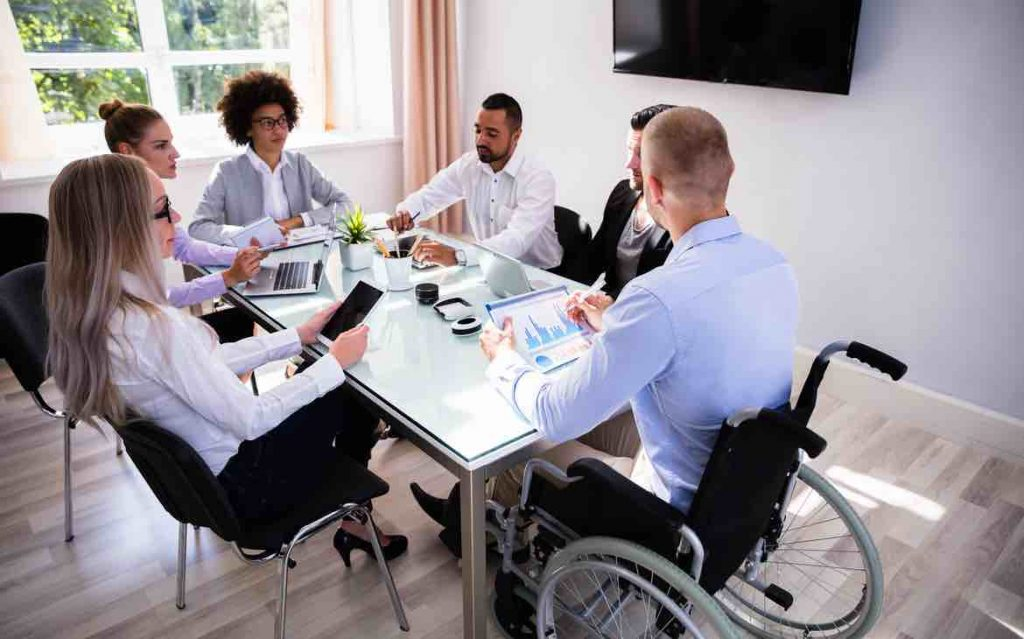 Disabled male in a wheelchair meeting with his colleagues at a table