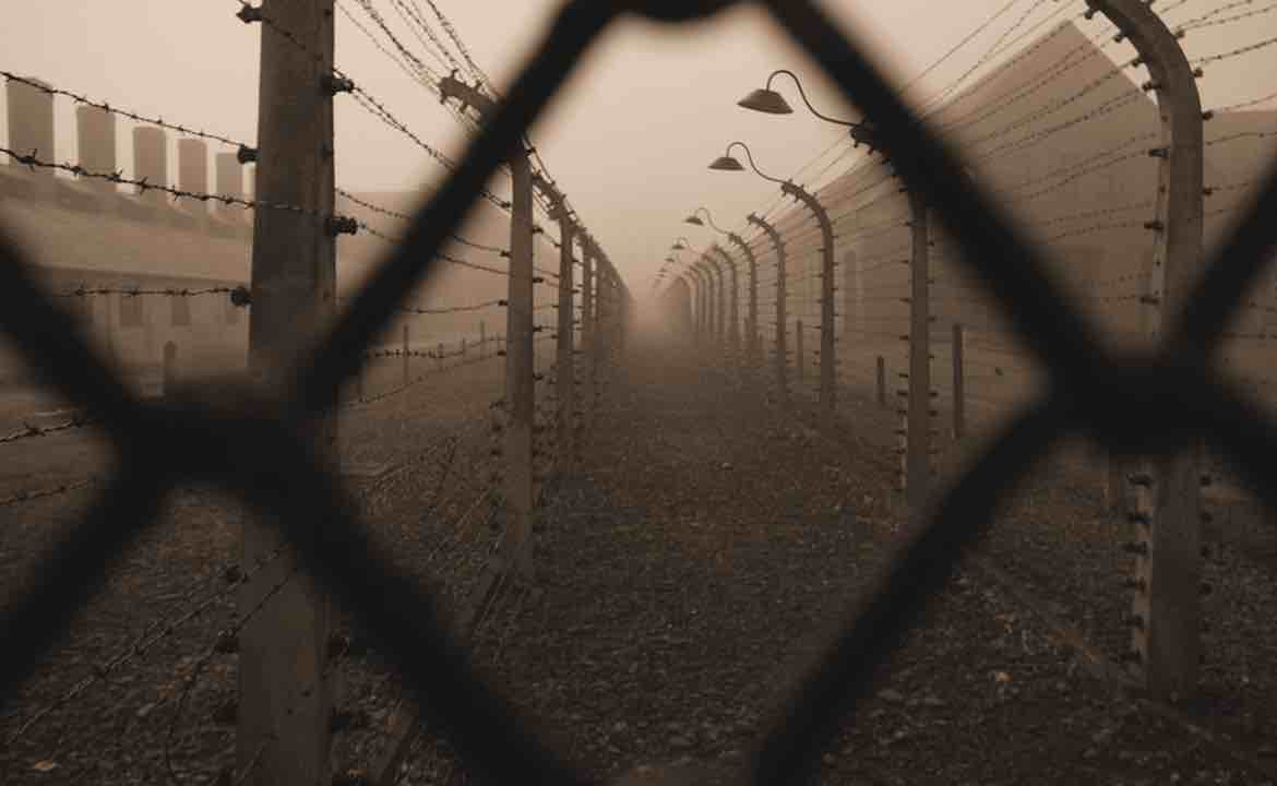 Looking through a wire fence of Auschwitz-Birkenau concentration camp