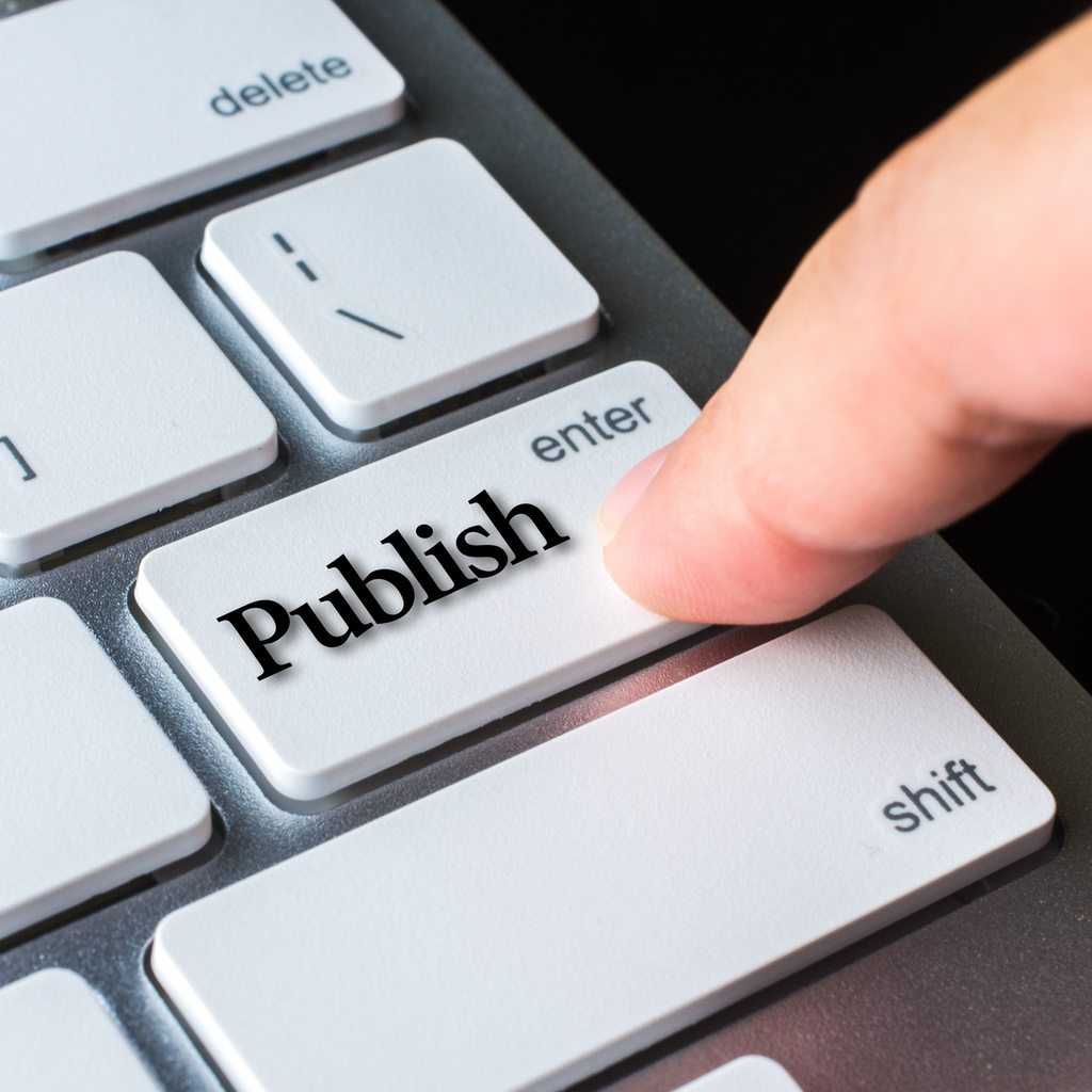 """A finger pressing on a computer keyboard key with the word """"Publish"""" written across it"""