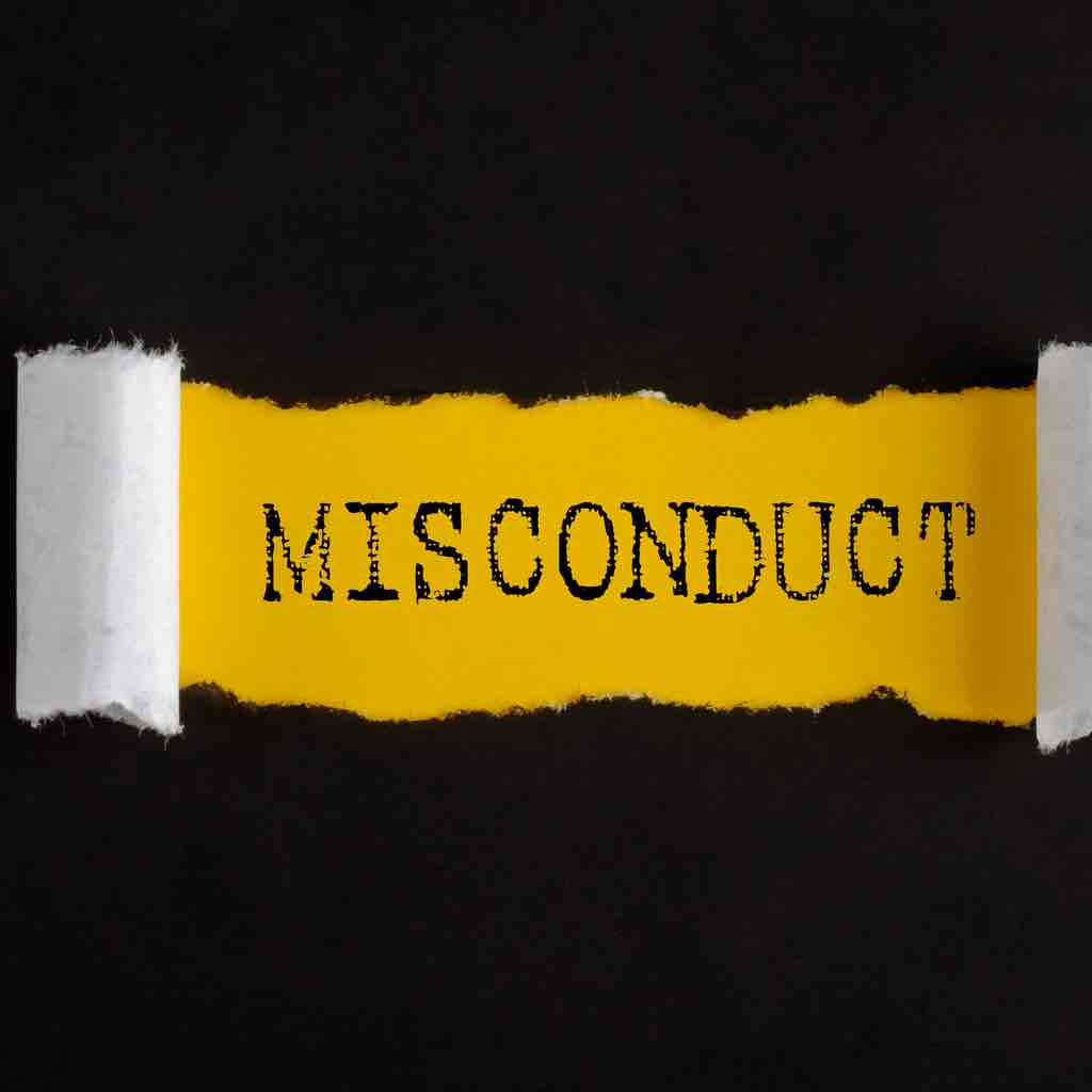 The word misconduct viewed through a tear in a black sheet