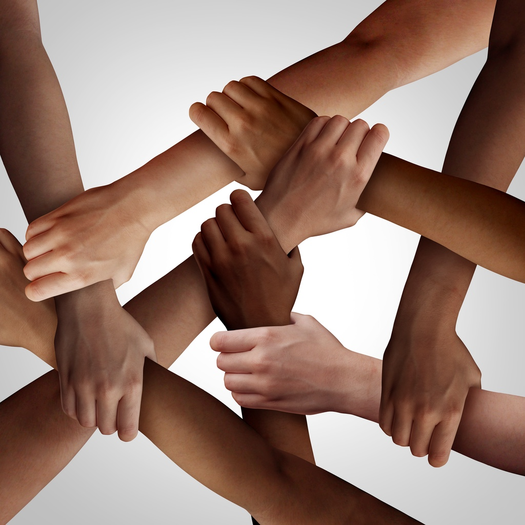 A web of multicultural arms and hands clasped together