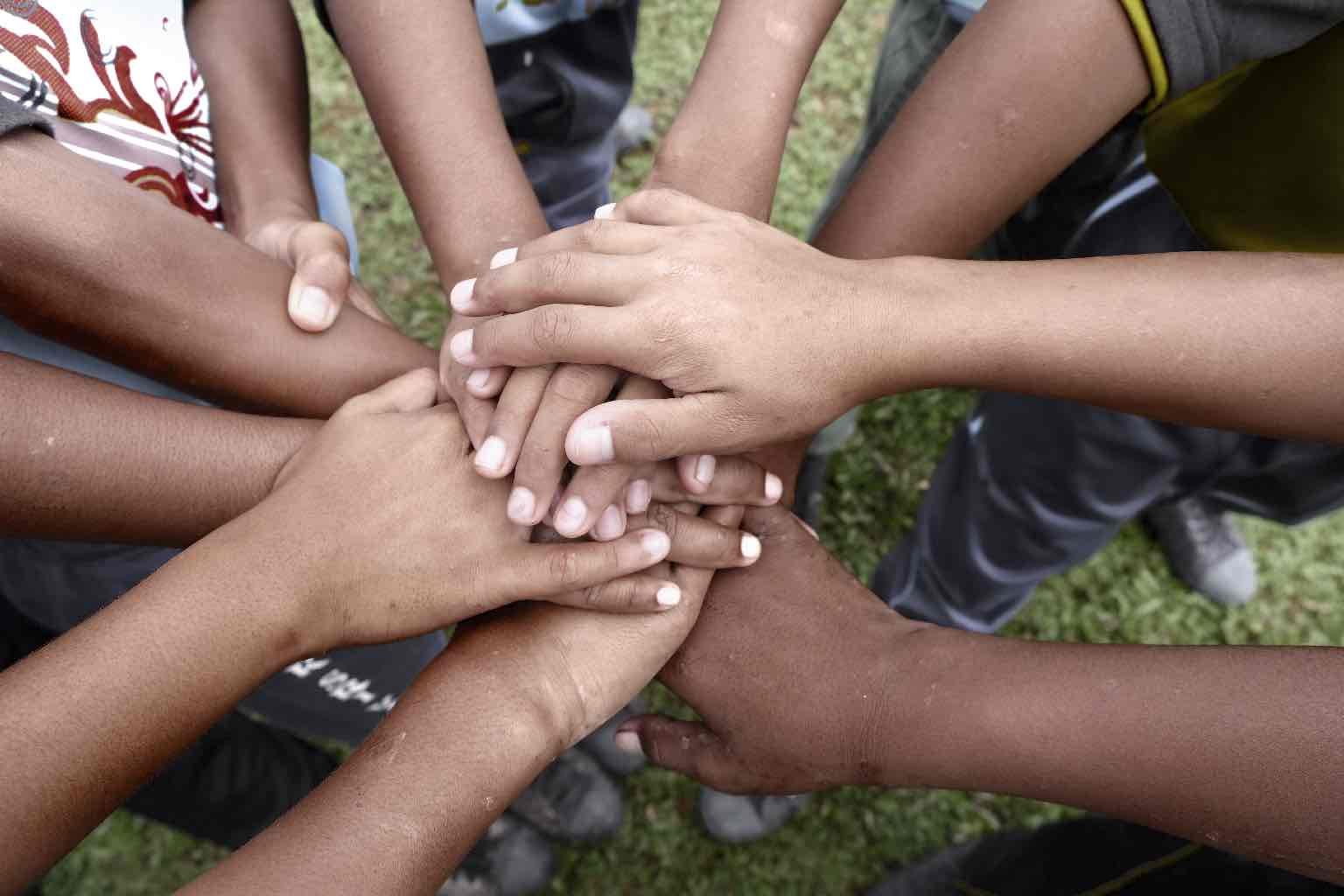 A circle of Indigenous hands and arms joining in the middle