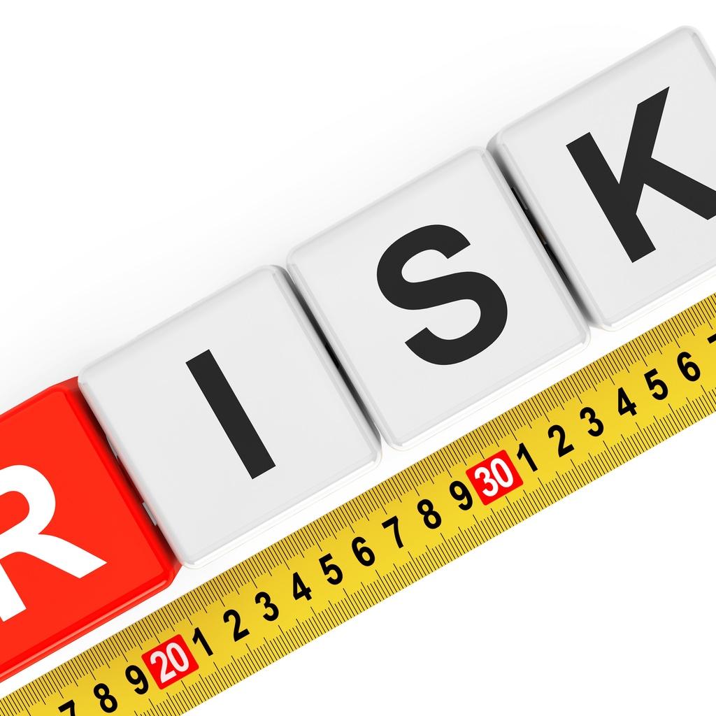 """The word """"RISK"""" written across tiles, with a tape measure immediately below."""