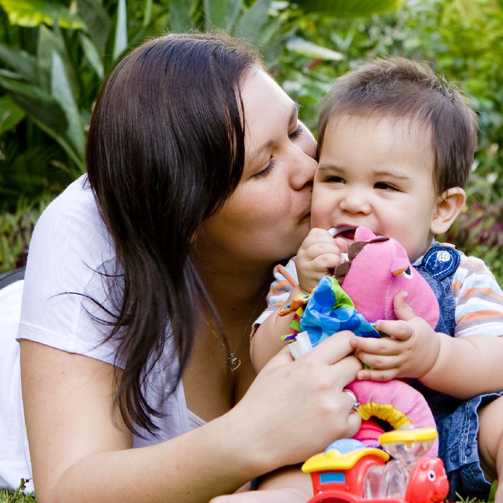 A Māori toddler share a hug and kiss
