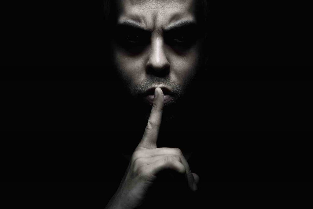 A menacing man in shadow holding a finger to his lips