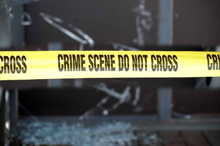 Yellow tape blocks off a crime scene with broken glass