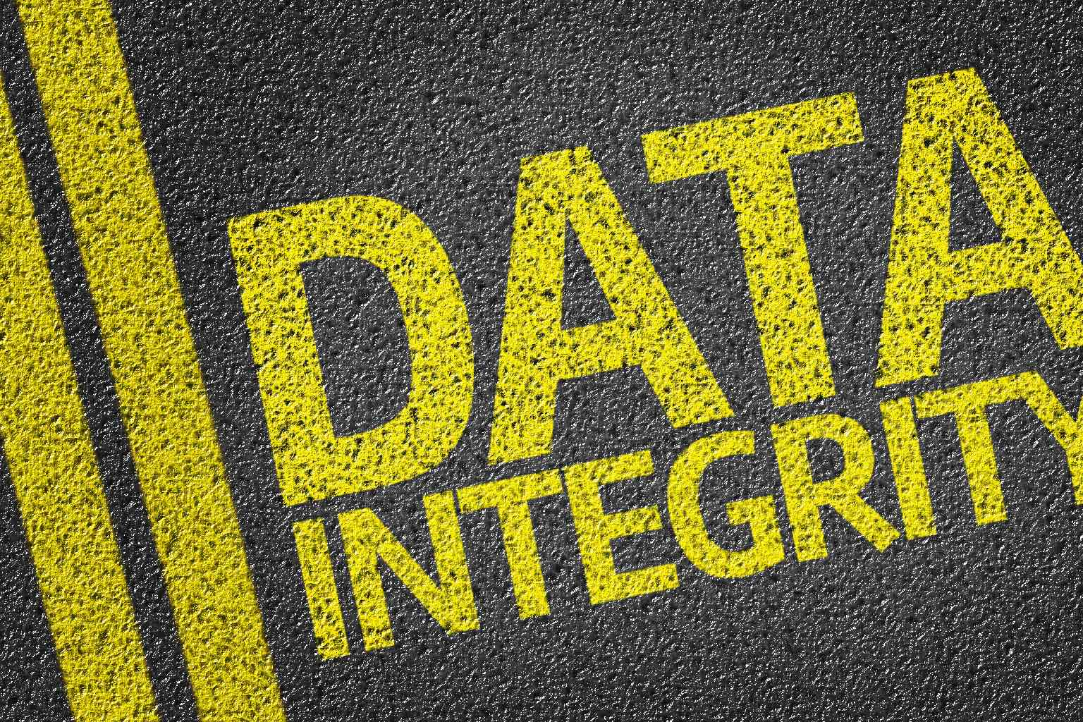 """The words """"DATA INTEGRITY"""" written on the road in yellow beside double yellow lines"""