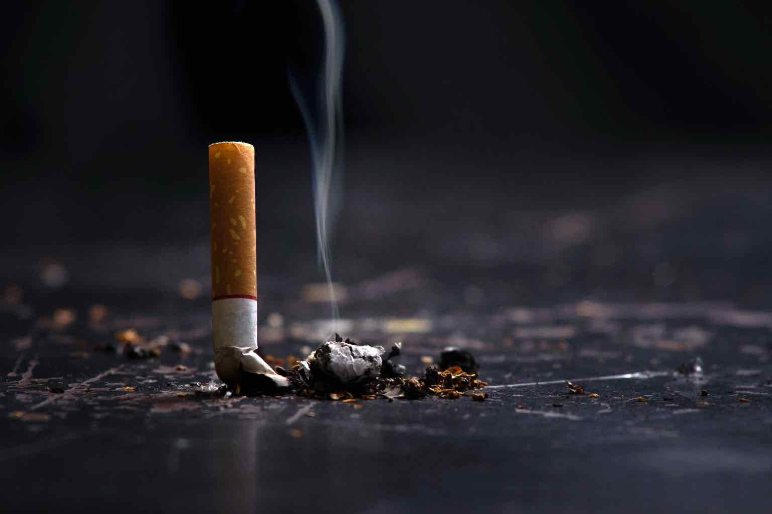 A stubbed cigarette with smoke rising from the ash