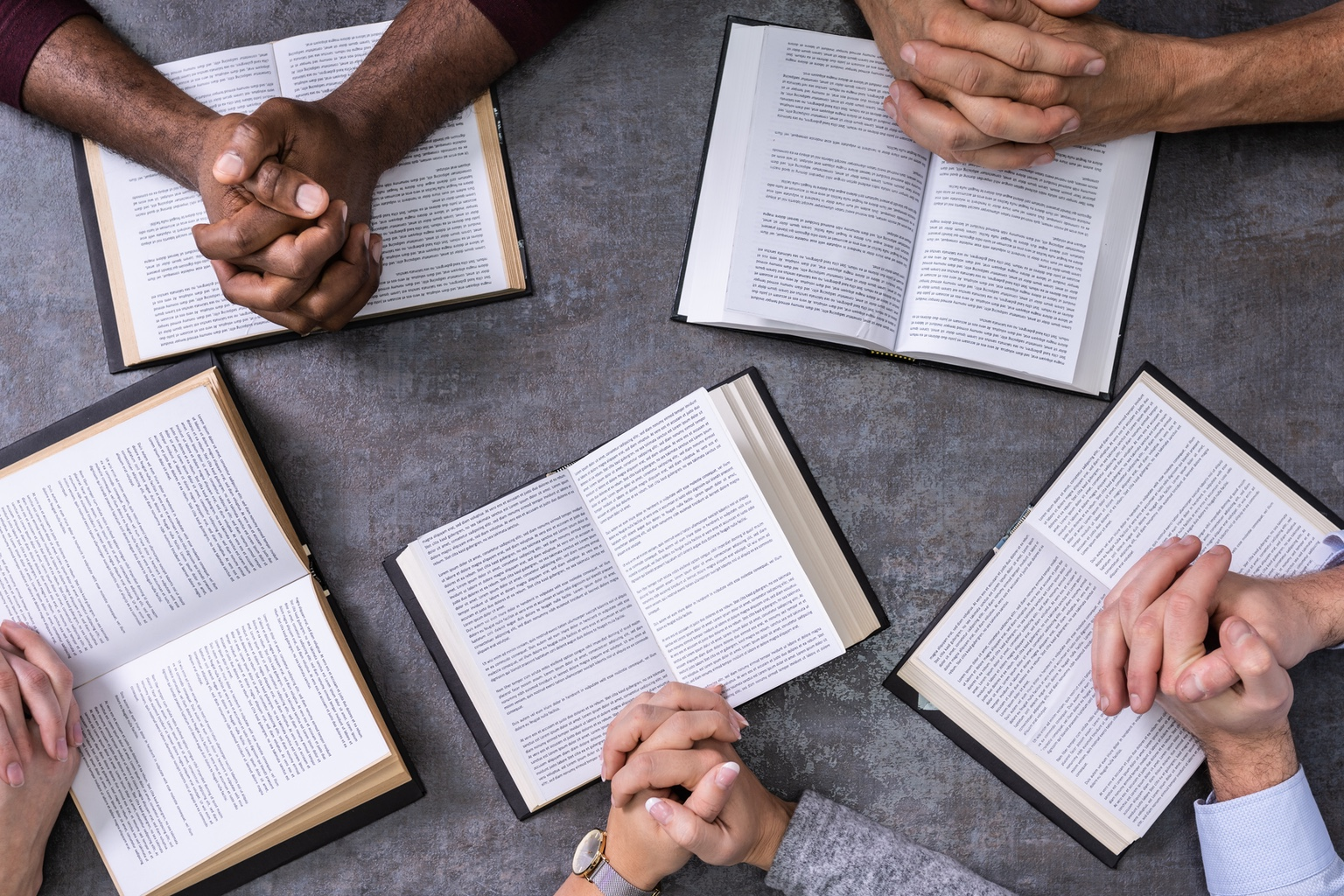 Elevated view of a diverse group of people reading books around a table
