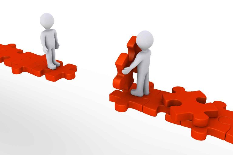 Two 3d figures attempting to bridge a gap using jigsaw pieces