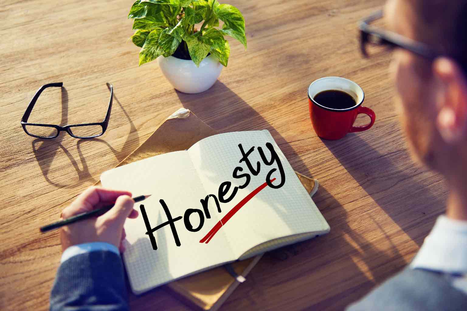 """A man working at a wooden desk with a pad in front of him with the underlined word """"Honesty"""""""