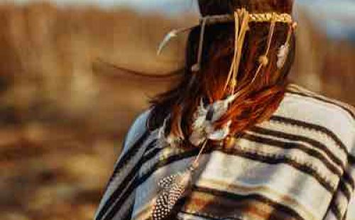 Back of First People woman walking in mountains in evening, hair with feathers