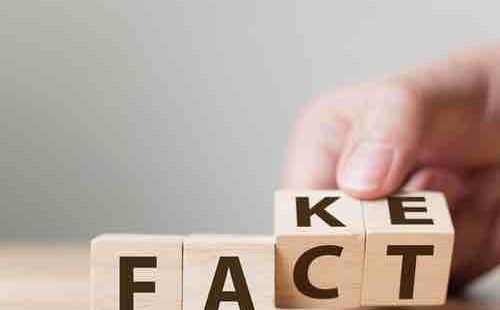A hand rolling two blocks to turn FACT into FAKE