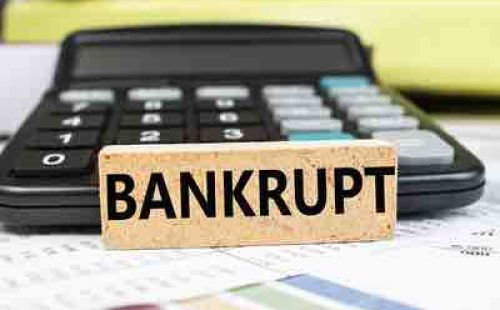 The word bankrupt is written on a wooden cube that stands on a financial document on a blurred background of a black calculator. Business and financial concept